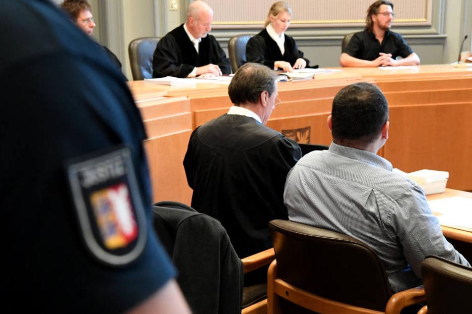 Der 41-Järhige sitzt neben seinem Anwalt im Kieler Landgericht.