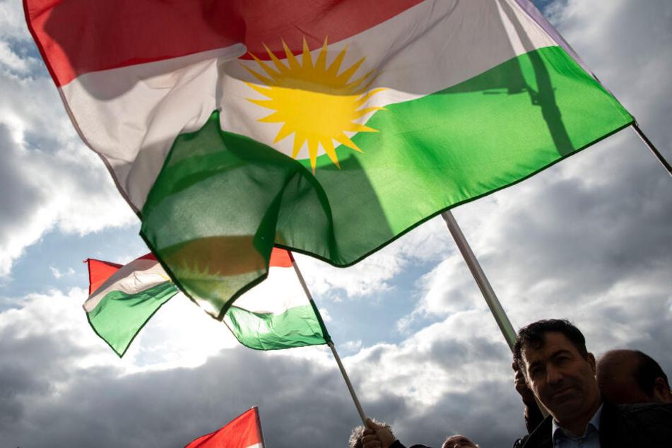 Demonstranten halten bei einer Protestaktion gegen die türkische Militäroffensive in Nordsyrien am Pariser Platz Fahnen der Autonomen Region Kurdistan.