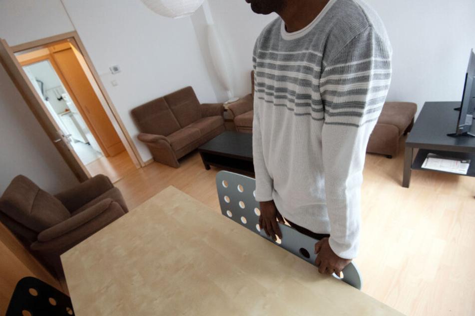 Ein Bewohner lehnt sich an einen Stuhl im Wohnzimmer der Männerschutzwohnung.