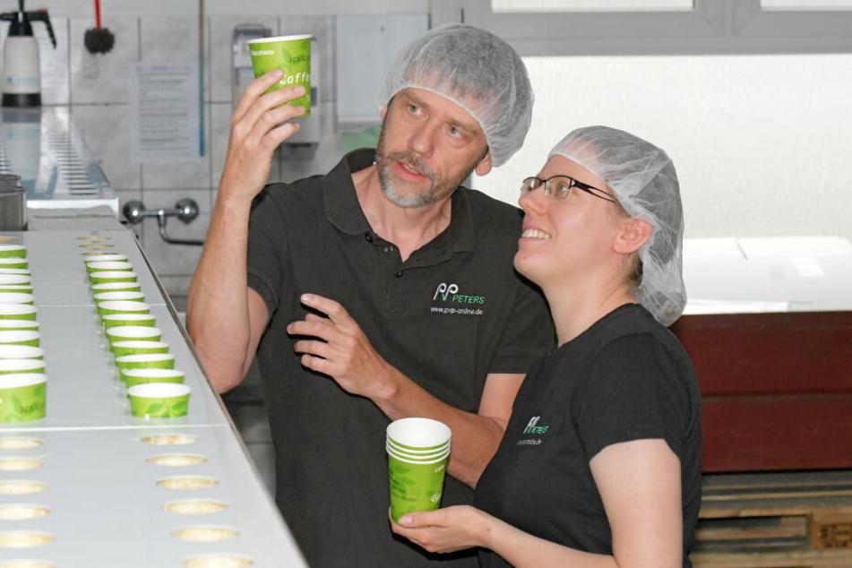 Mitarbeiter Volker Braun und Stefanie Lange bei der Qualitätskontrolle von Kaffeebechern.