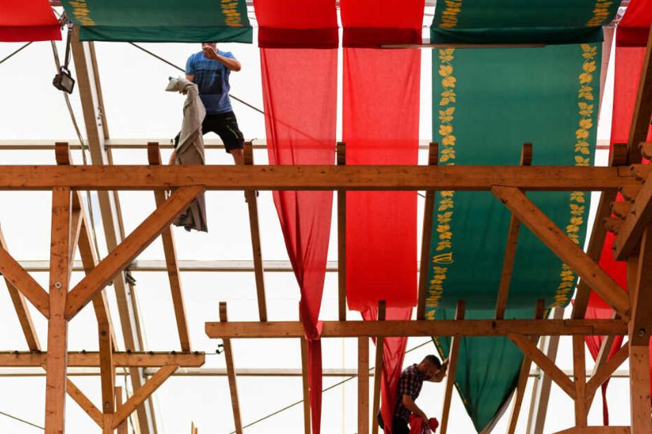 Zwei Arbeiter befestigen bei einem Bierzelt Stoffbänder an der Decke.