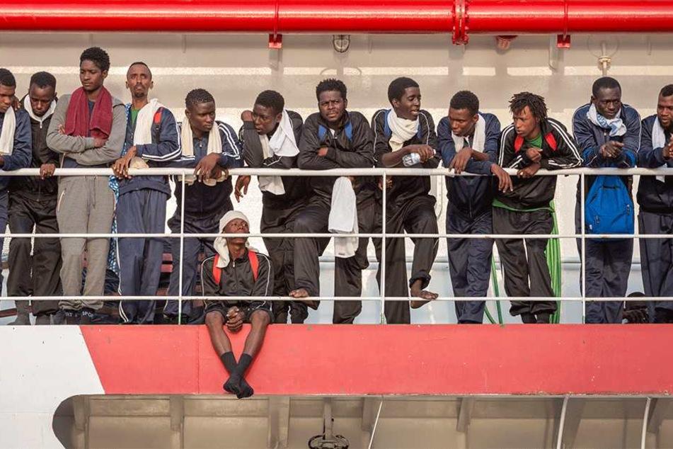 """Flüchtlinge stehen am 14. Juli in Salerno (Italien) an Bord eines Rettungsschiffs der NGO """"Ärzte ohne Grenzen"""". Das Schiff ist mit mehr als 900 Flüchtlingen an Bord im Hafen von Salerno eingelaufen."""