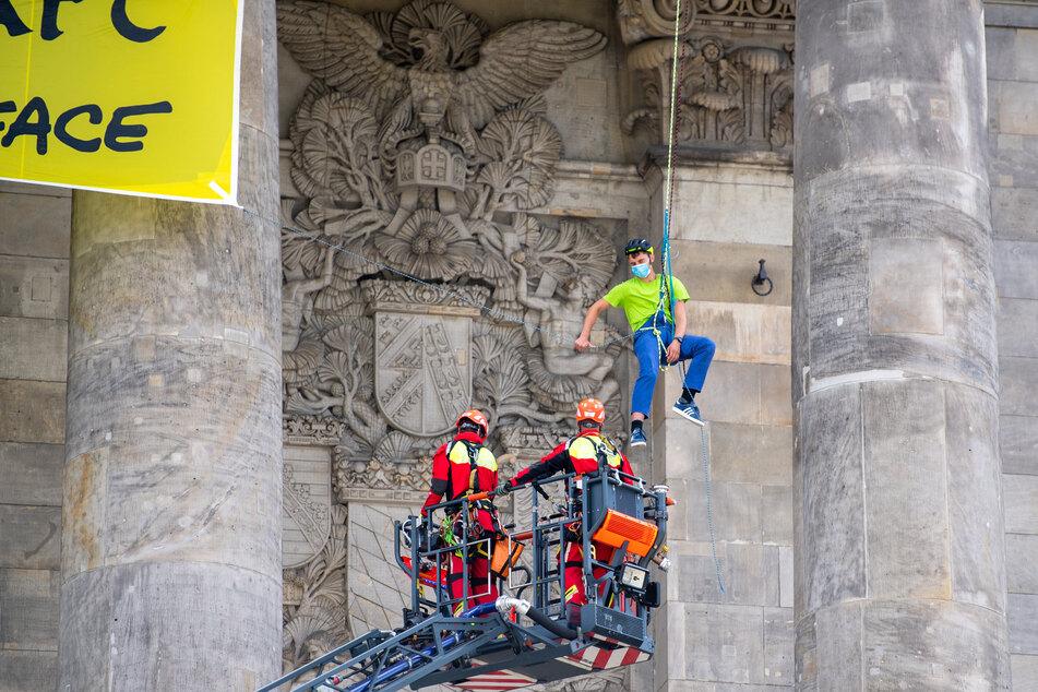 Ein Höhenrettungsteam der Feuerwehr wird im Kranwagen zu einem Greenpeace-Aktivisten am Reichstagsgebäude gefahren, der sich mit anderen Aktivisten mit einem Transparent am Gebäude abgeseilt hatte.