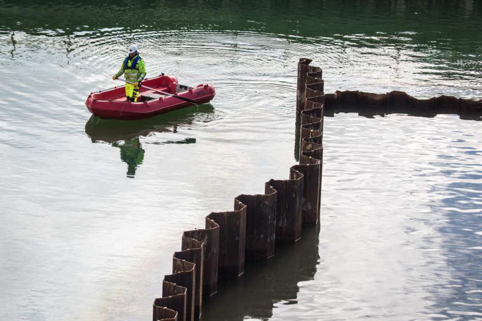 Ein Mitarbeiter einer Spezialfirma für Unterwasserarbeiten schippert über die mit Grundwasser vollgelaufenen Baugrube.