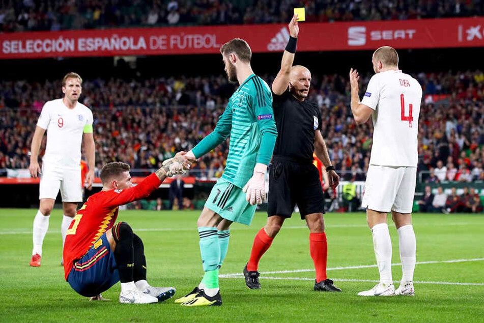 ...und bekommt dafür vom polnischen Schiedsrichter Szymon Marciniak (Zweiter von rechts) die Gelbe Karte, während Spaniens Keeper David de Gea (Vorne, Zweiter von links) Sergio Ramos (Vorne, Erster von links) aufhilft.