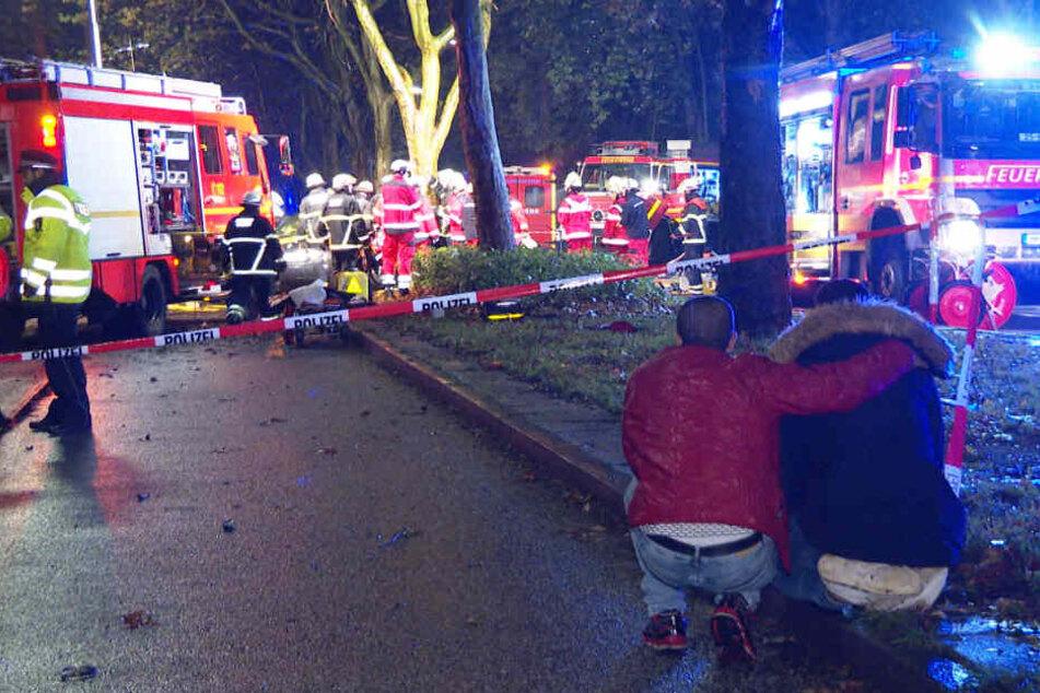 Zwei unverletzte Insassen aus einem der Unfallfahrzeuge beobachten die Rettungsaktion.