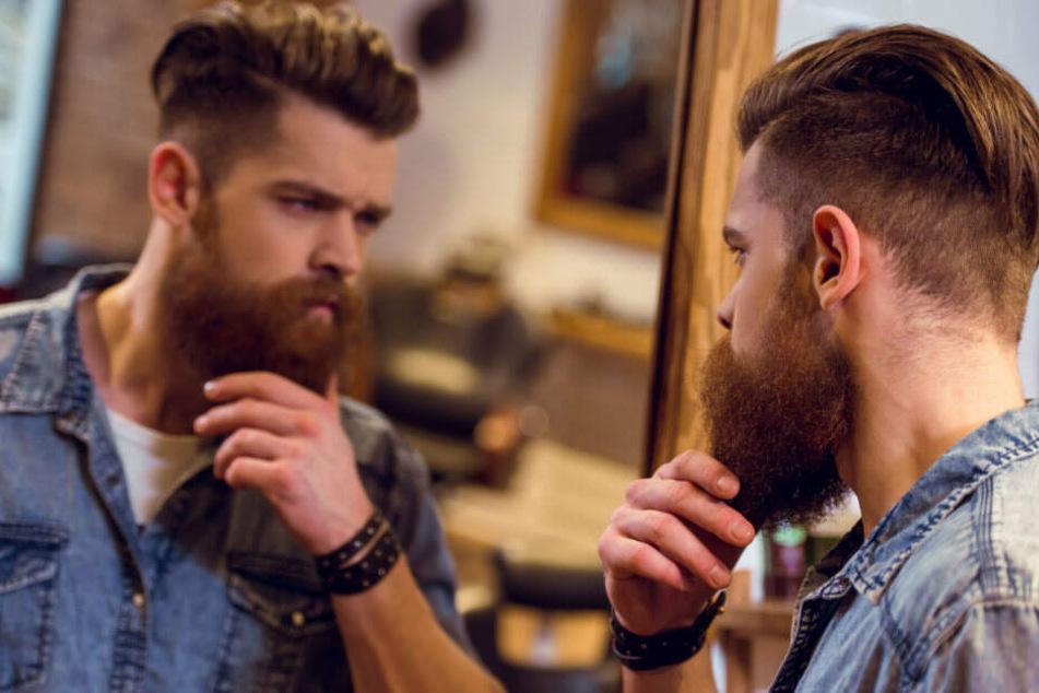 Ein Hipster betrachtet sich im Spiegel. (Symbolbild)