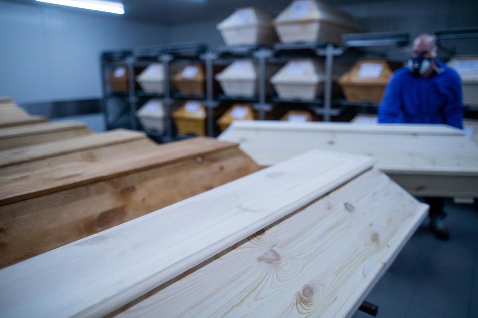 Ein Mitarbeiter bereitet einen Verstorbenen in einem Sarg auf die ärztliche Leichenschau vor.