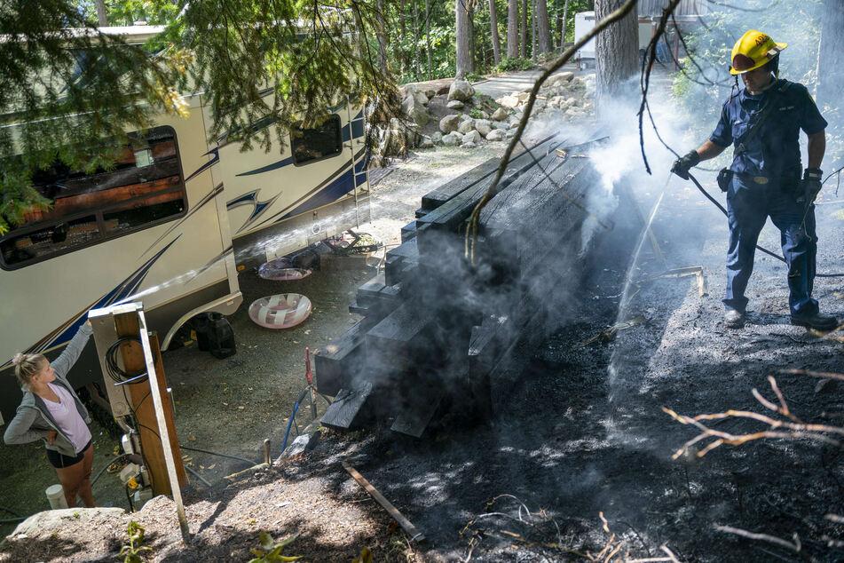 Ein Feuerwehrmann des Department of Natural Resources löscht einen Holzstapel in Bellingham.