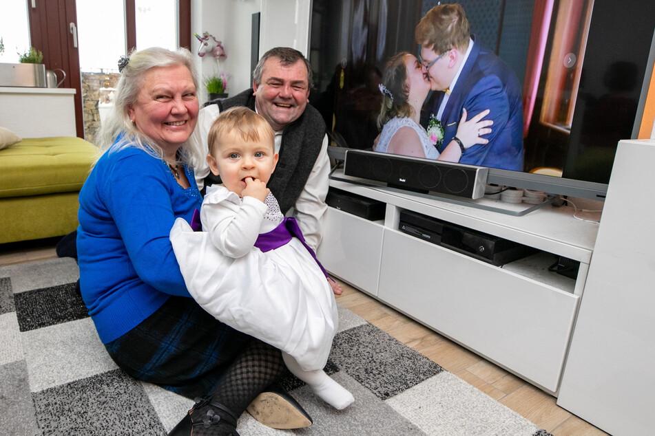 Zu Hause gucken sich Viktor Kromer (58) und seine Frau Erna (58) mit ihrem Enkelkind Liv die Hochzeit an - Kuss der Frischvermählten inklusive.