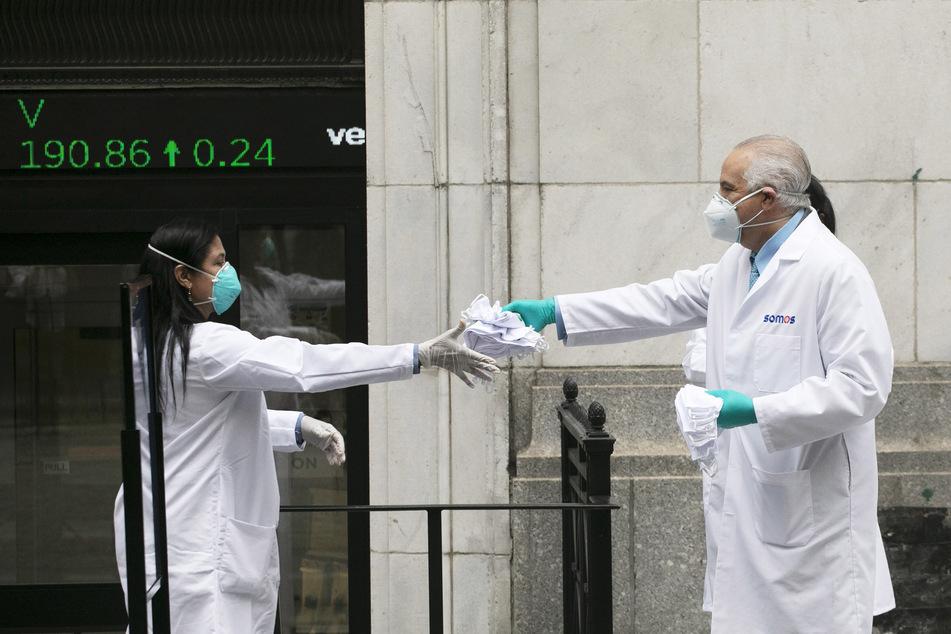 Mitarbeiter des Gesundheitswesens bereiten sich darauf vor, Mundschutze an der New Yorker Börse zu verteilen. (Symbolbild)