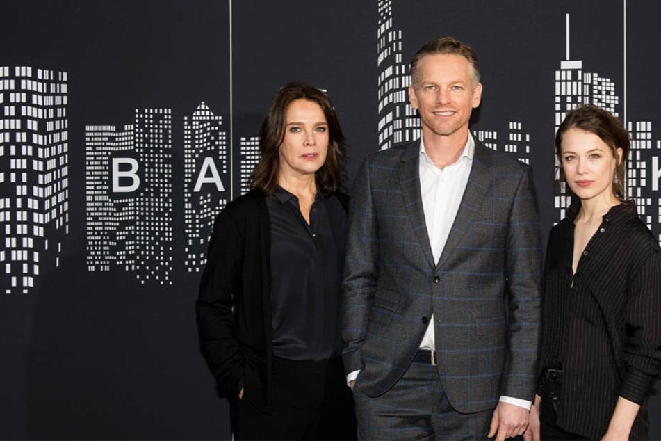 """Die Schauspieler Desiree Nosbusch (l-r), Barry Atsma und Paula Beer schauen bei einem Fototermin zum ZDF-Mehrteiler """"Bad Banks"""" in die Kamera."""