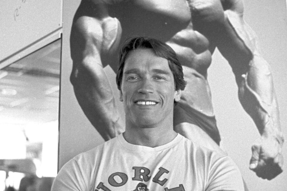 Der österreichische Schauspieler Arnold Schwarzenegger steht in München vor einem Poster, das ihn als Bodybuilder zeigt. (Archivbild)
