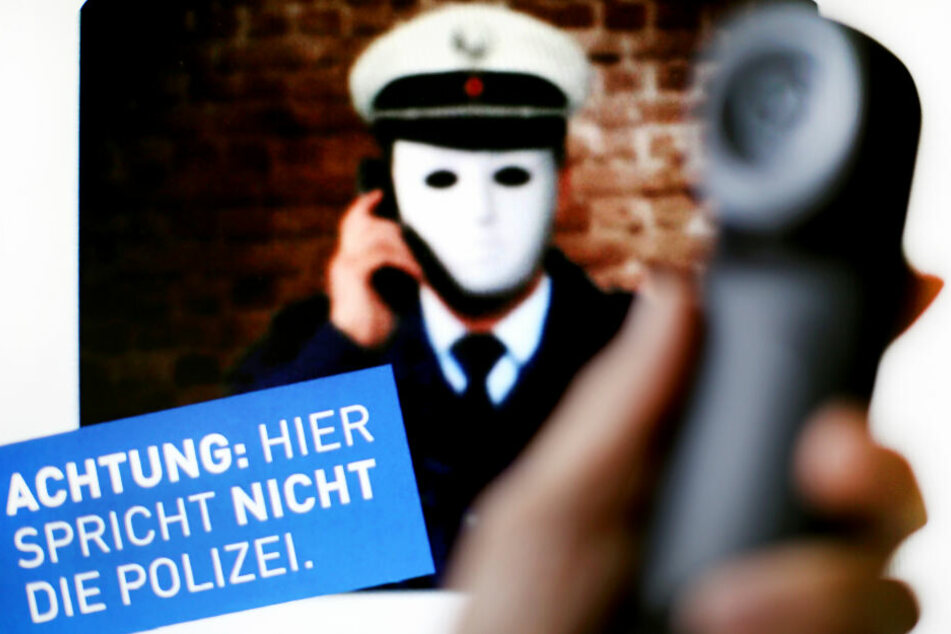 """Ein Telefonhörer ist vor einem Plakat der Polizei mit der Aufschrift """"Achtung: Hier spricht nicht die Polizei"""" zu sehen."""
