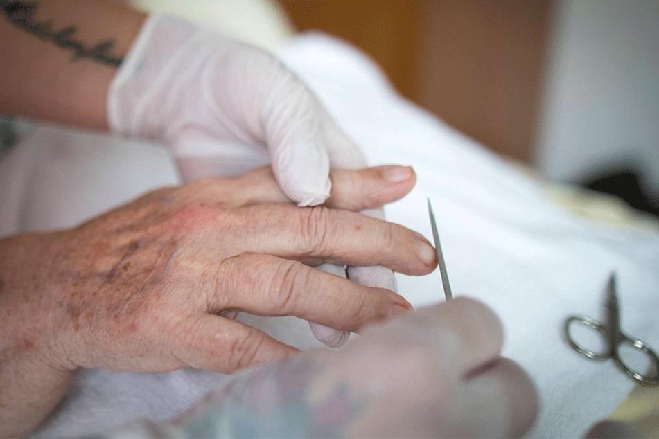 Eine Pflegerin feilt einer Bewohnerin die Nägel.