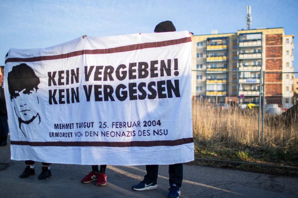 """Linke Demonstranten halten am Rande der Gedenkstunde am Todestag des NSU-Opfers Mehmet Turgut am Tatort ein Transparent mit der Aufschrift """"Kein Vergeben! Kein Vergessen""""."""