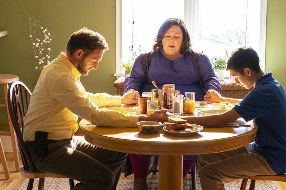Joyce (M., Chrissy Metz), ihr Sohn John (r., Marcel Ruiz) und ihr Mann Brian (Josh Lucas) beten gemeinsam am Küchentisch, bevor sie anfangen zu essen.