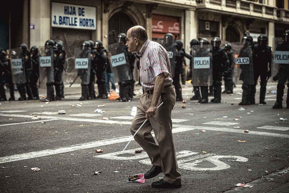 Ein Mann geht während einer Demonstration in Bracelona an einer Barrikade von Polizisten vorbei.