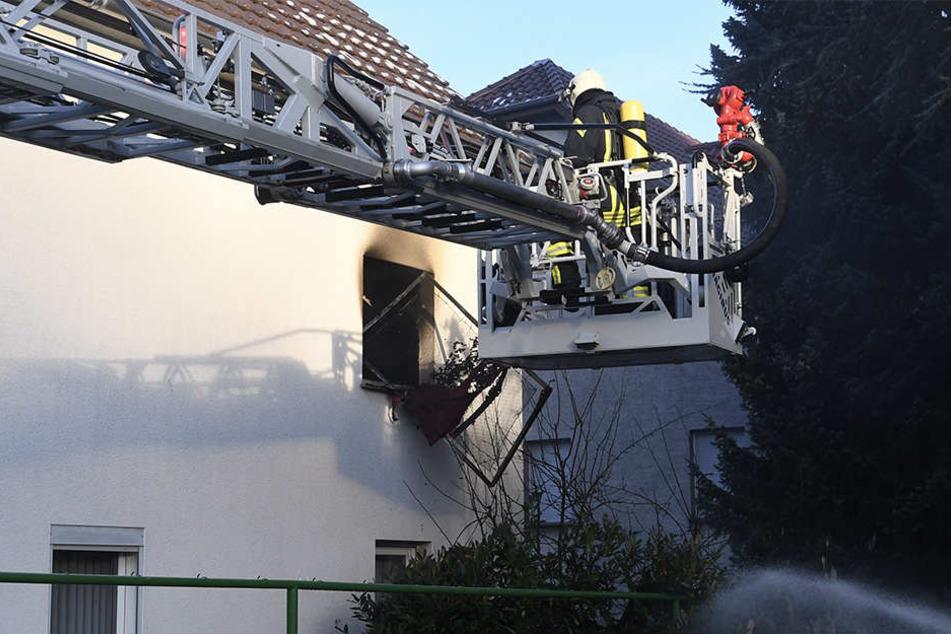 Feuerwehrleute bringen ein ausgebranntes Bettgestell ins Freie.