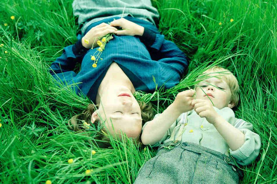 Astrid Lindgren (Alba August) entspannt mit ihrem Sohn Lasse (Marius Damslev) im Gras.