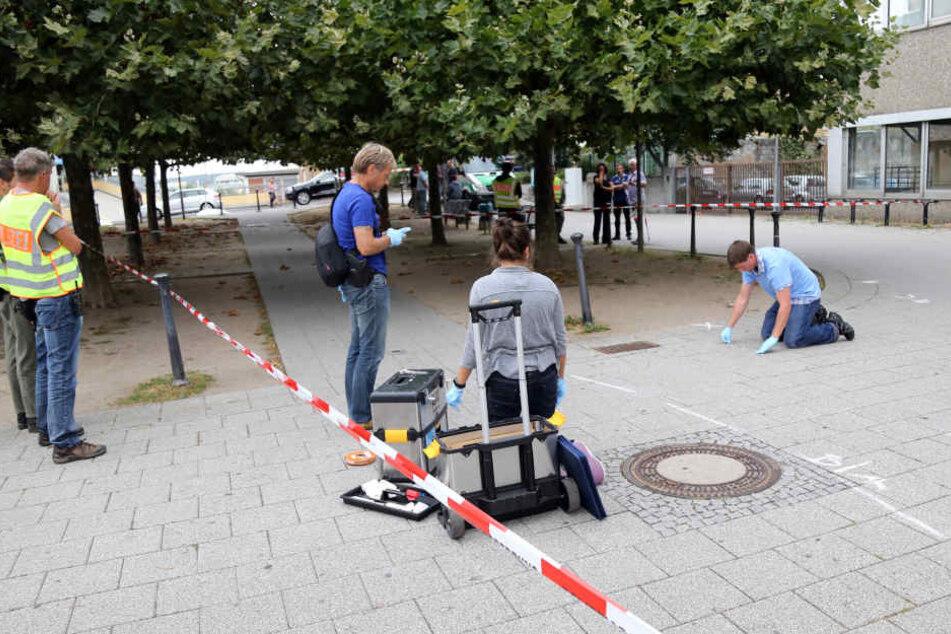 Polizisten nehmen in Aschaffenburg Spuren auf. Hier hat der Mann dem Fußgänger das Messer in den Rücken gerammt.