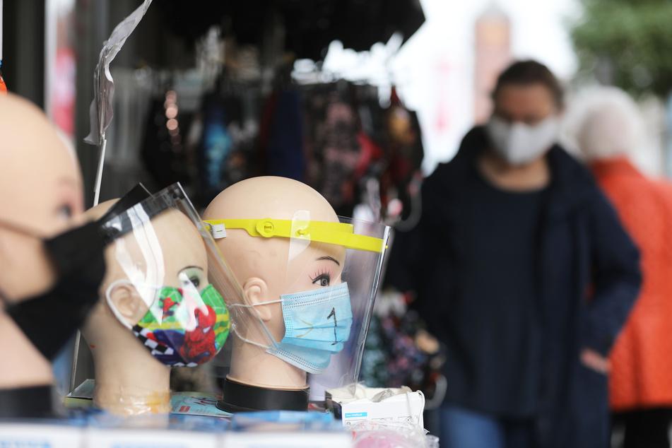 Passanten gehen an einem Geschäft vorbei, das Masken und Gesichtsschilder verkauft.