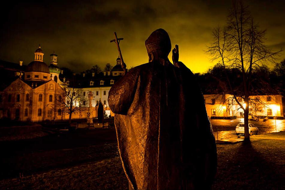 Eine Bronzestatue vor dem Kloster St. Marienthal erinnert an Johannes Paul II. Durch die Beleuchtung der Tomatenreiferie in Bogatynia, Polen, ist zu den Abendstunden ein heller Schein zu sehen.