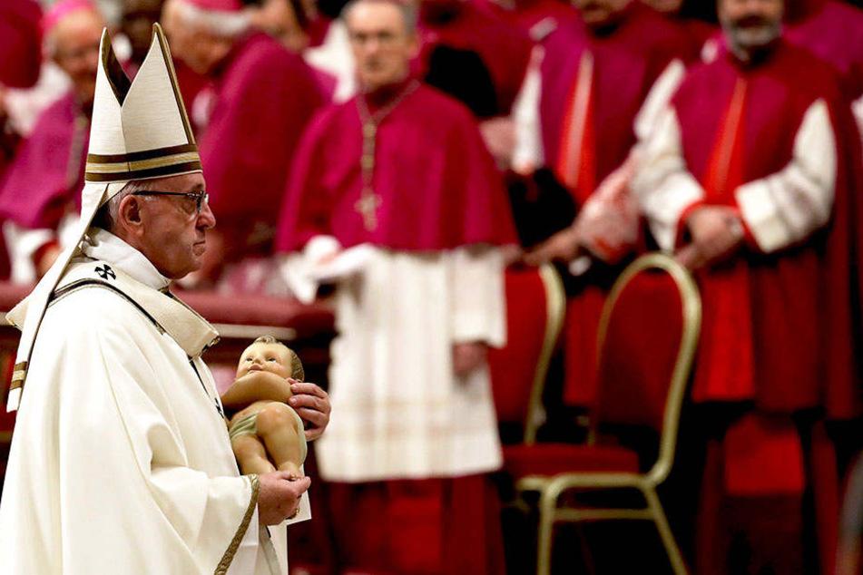 Während der Messe hält der Pontifex eine Jesusfigur in der Hand.