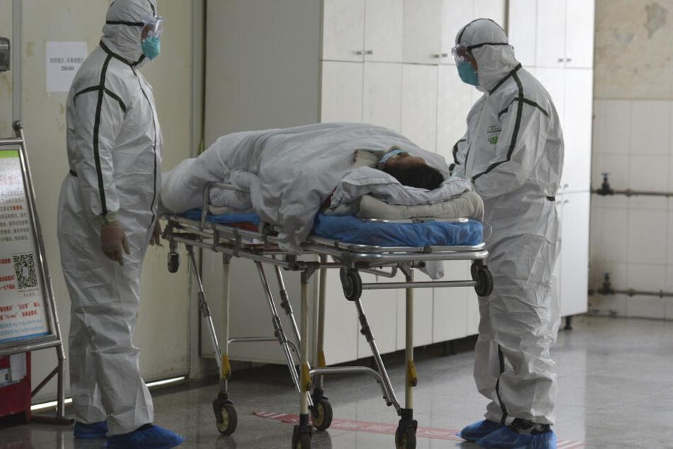 Medizinisches Personal in Schutzanzügen verlegt einen Coronavirus-Patienten in eine Isolierstation in China. (Archivbild)