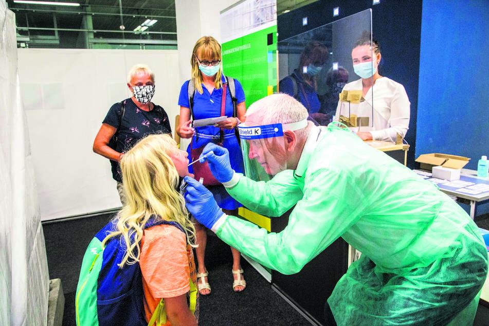 Während Dr. Klaus Heckemann (64) bei Irene (7) einen Abstrich nimmt, warten ihre Mutti und Oma im Hintergrund auf ihren Test. Ärztin Julia Heckemann (24) kennzeichnet die Teströhrchen anschließend mit einem Barcode.