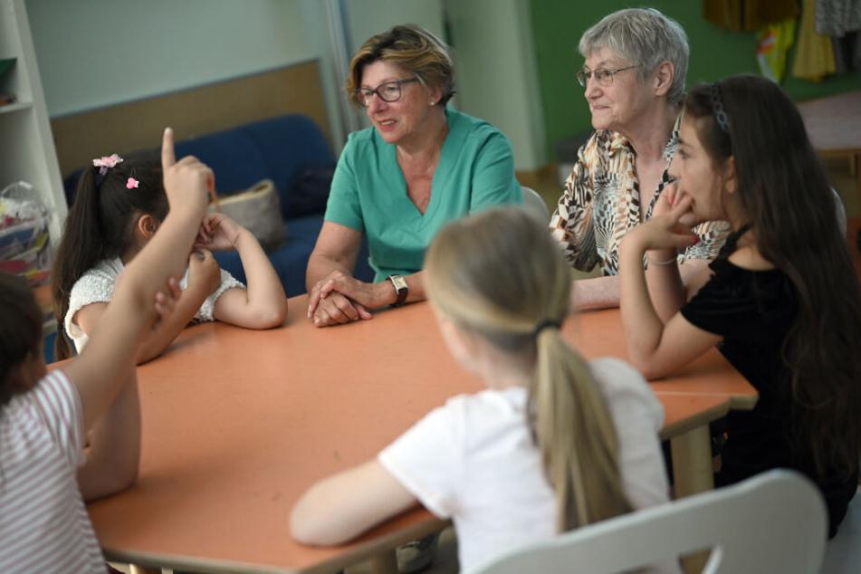 Die Streitschlichterinnen Barbara Savelsbergh (l) und Dagmar Knopf-Kaupert (r) sitzen mit Kindern an einem Tisch in einer Kölner Grundschule.