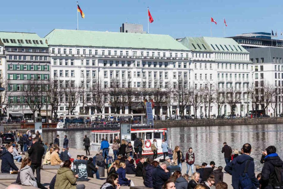 Zahlreiche Menschen sitzen bei Sonnenwetter an der Alster in Hamburg. Hier wollen am Dienstag Beschäftigte im öffentlichen Dienst aus Protest baden gehen.