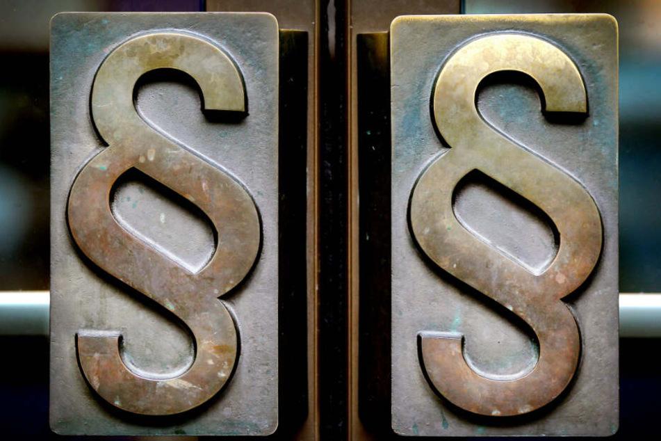 Paragrafen-Symbole prangen an Türgriffen am Eingang eines deutschen Landgerichts. (Symbolbild)