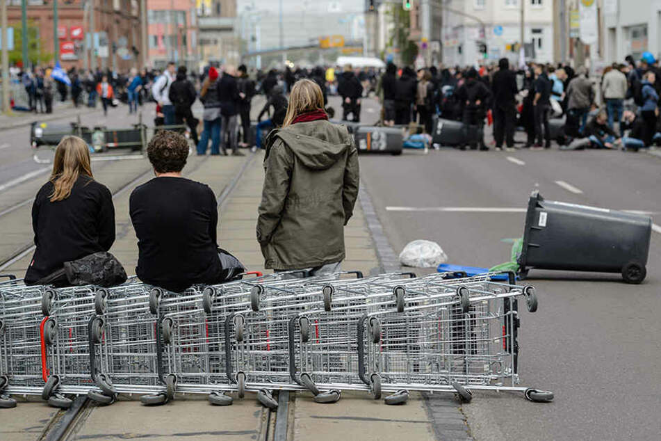 Teilnehmer einer Demonstration gegen einen geplanten Aufmarsch der rechten Szene haben am Straßenbarrikaden mit Mülltonnen und Einkaufswagen errichtet.