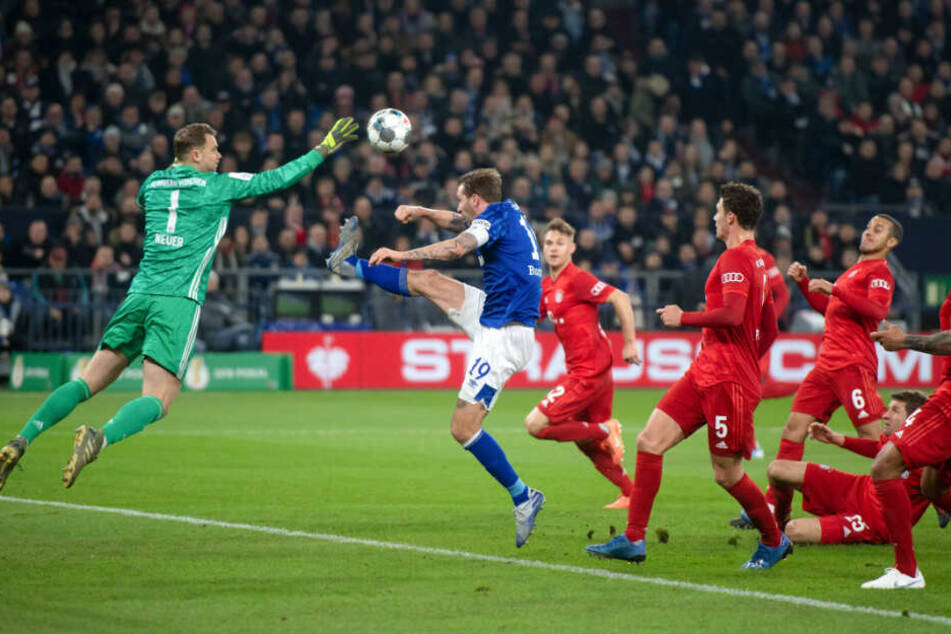 Manuel Neuer wehrt den Ball kurz vor dem heranrauschenden Guido Burgstaller ab.
