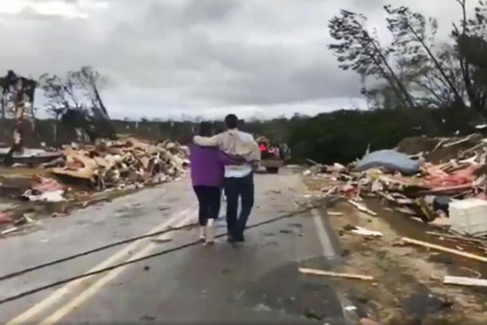 Menschen gehen durch Trümmer, nachdem ein Tornado in der Gegend wütete.