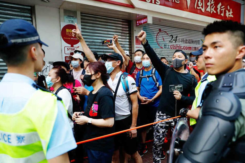 Demonstranten werden in Hong Kong von der Polizei zurückgehalten.