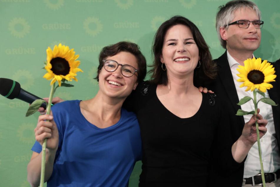 Hannah Neumann (l.), Annalena Baerbock (m.) und Sven Giegold (r.) lächeln nach der Bekanngabe der ersten Prognose für die Europawahl.