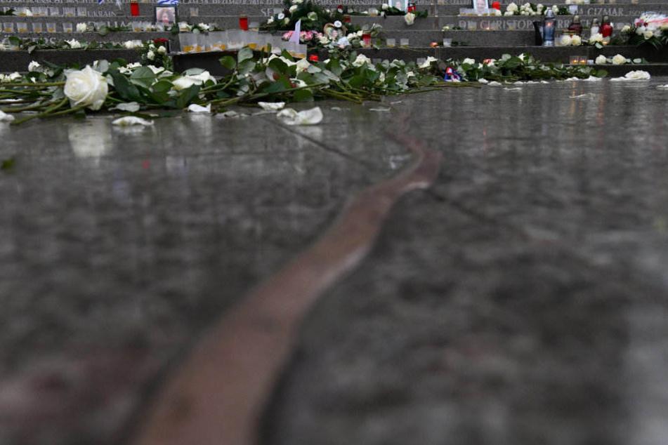 Ein Riss durch den Boden, Kerzen und Blumen, sowie die Namen an der Treppe erinnern an die Opfer des Anschlags.