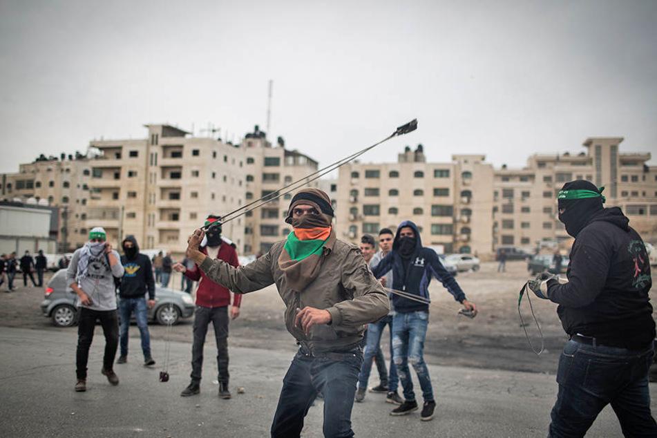 Palästinenser schleudern am 22.12.2017 in Ramallah im Westjordanland Steine auf israelische Soldaten.