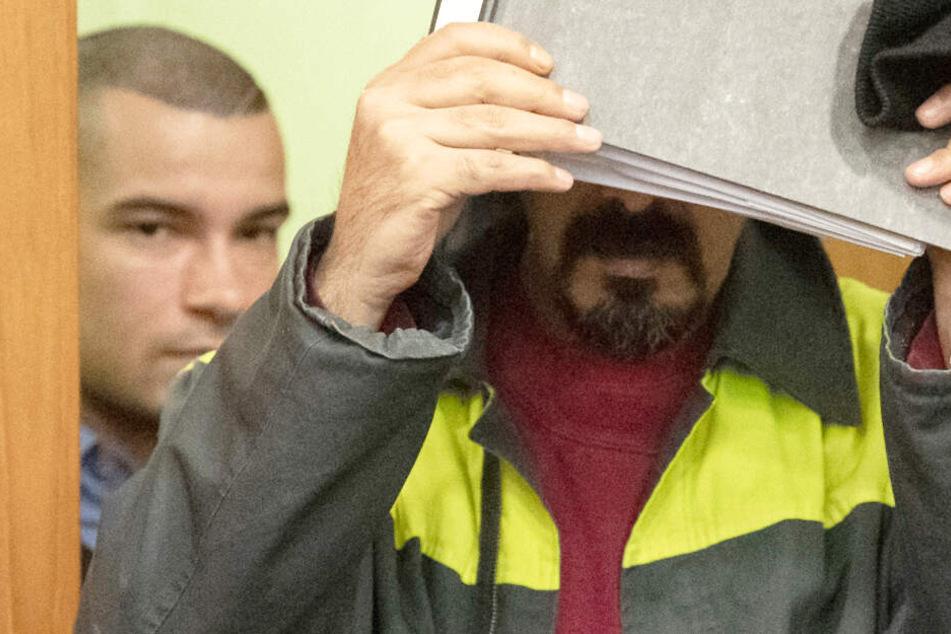 Mit einer Kladde vor dem Gesicht schützte sich der 33-jährige Angeklagte beim Betreten des Gerichtssaals vor den Kamerateams und Fotografen.