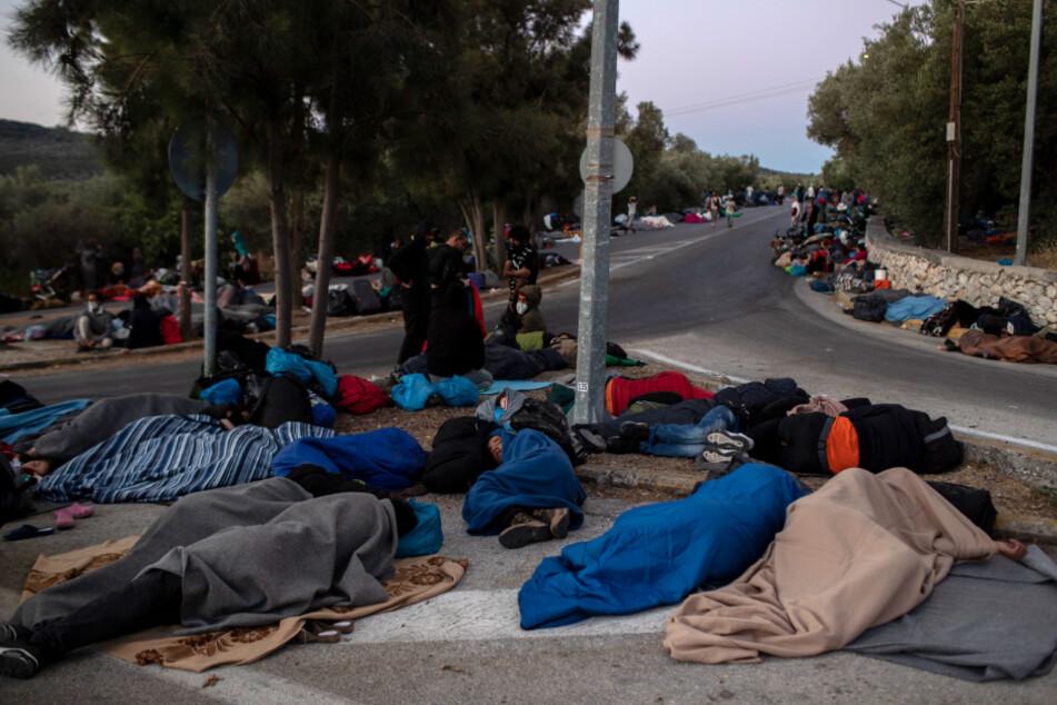 Migranten schlafen am Straßenrand in der Nähe des ausgebrannten Flüchtlingslagers Moria. Mehrere Brände haben das Lager fast vollständig zerstört.