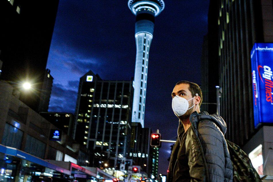 Ein Passant mit Mundschutz geht durch die Innenstadt in Auckland.