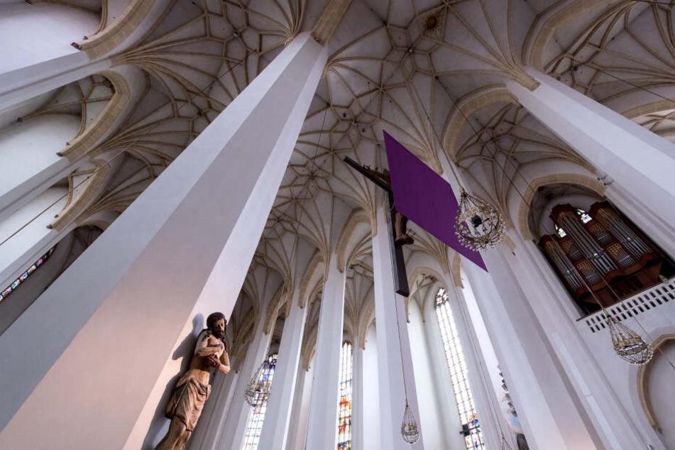Ein lila Tuch verhüllt in der Frauenkirche ein Kreuz. In vielen Kirchen werden Darstellungen von Jesus in der Zeit vor Ostern verhüllt.