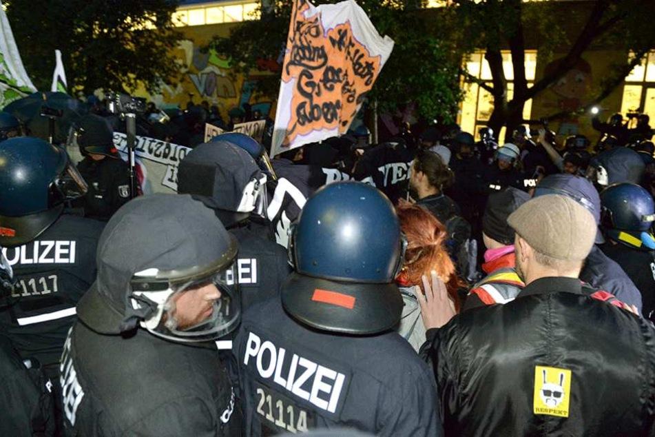 Polizisten stehen vor einem besetzten Haus auf der Rigaer Straße, wo linksautonome immer wieder Krawalle machen.