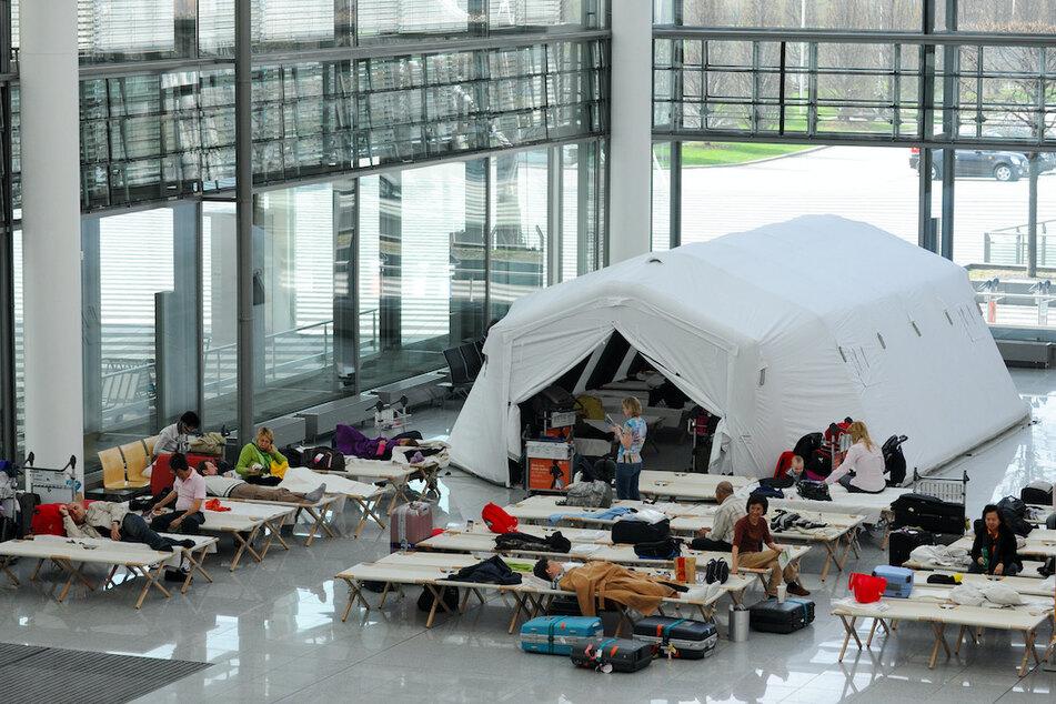 Fluggäste sitzen am am Flughafen auf Feldbetten in einer Notunterkunft im Terminal 2.