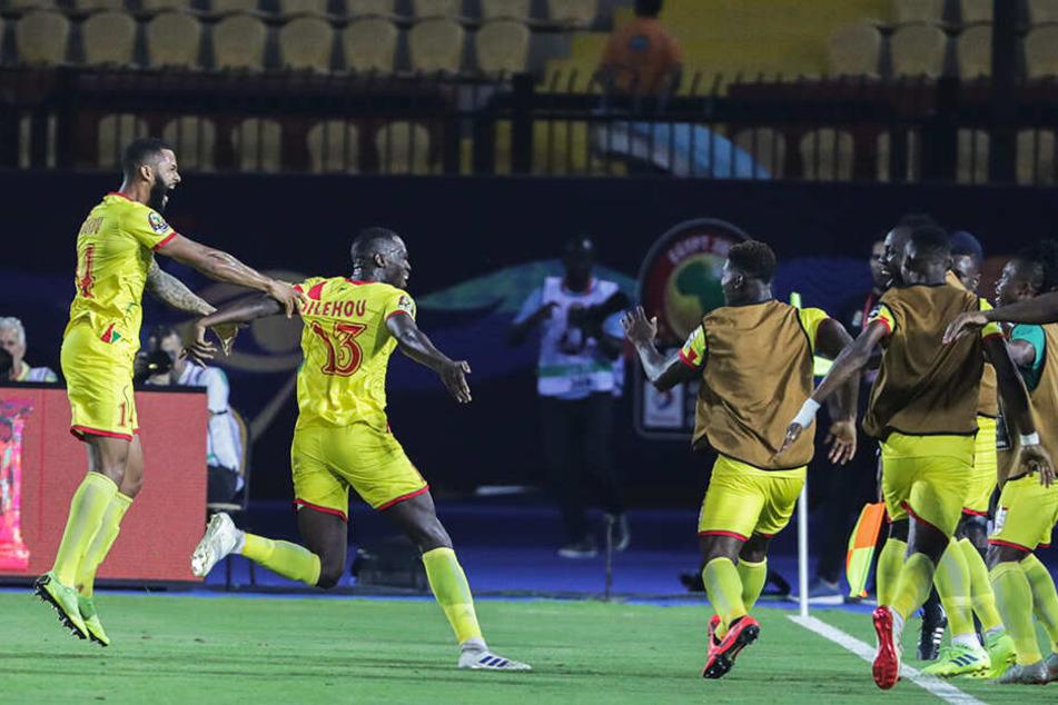 Cebio Soukou (l.) bejubelt mit seinen Mannschaftskollegen die zwischenzeitliche 1:0-Führung des Benin.