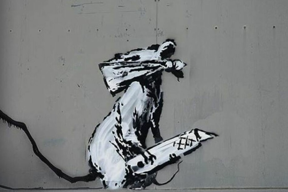 Banksys Werk stellt eine Ratte mit einem Bleistift und einer verdeckten Schnauze dar.