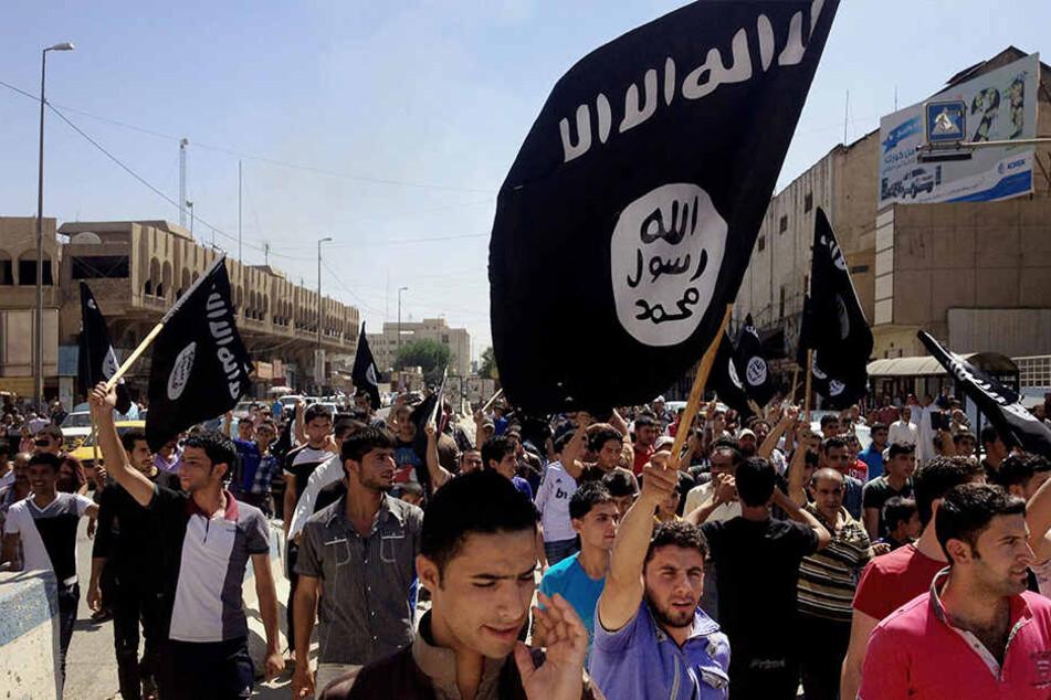 Irakische Unterstützer des Islamischen Staats demonstrieren und schwenken Flaggen des IS vor dem Hauptsitz der Regierung in Mosul.