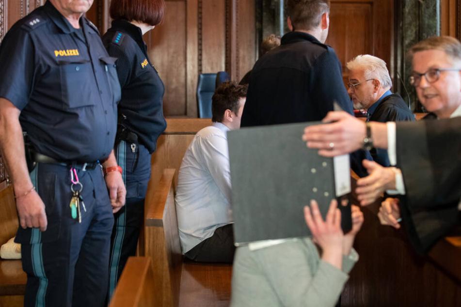 Ein 26-Jähriger (M) und dessen Ehefrau (v) sitzen auf der Anklagebank im Sitzungssaal im Landgericht Nürnberg-Fürth. Das wegen zweifachen Mordes angeklagte Paar soll zunächst versucht haben, die Mutter des Mannes zu vergiften.